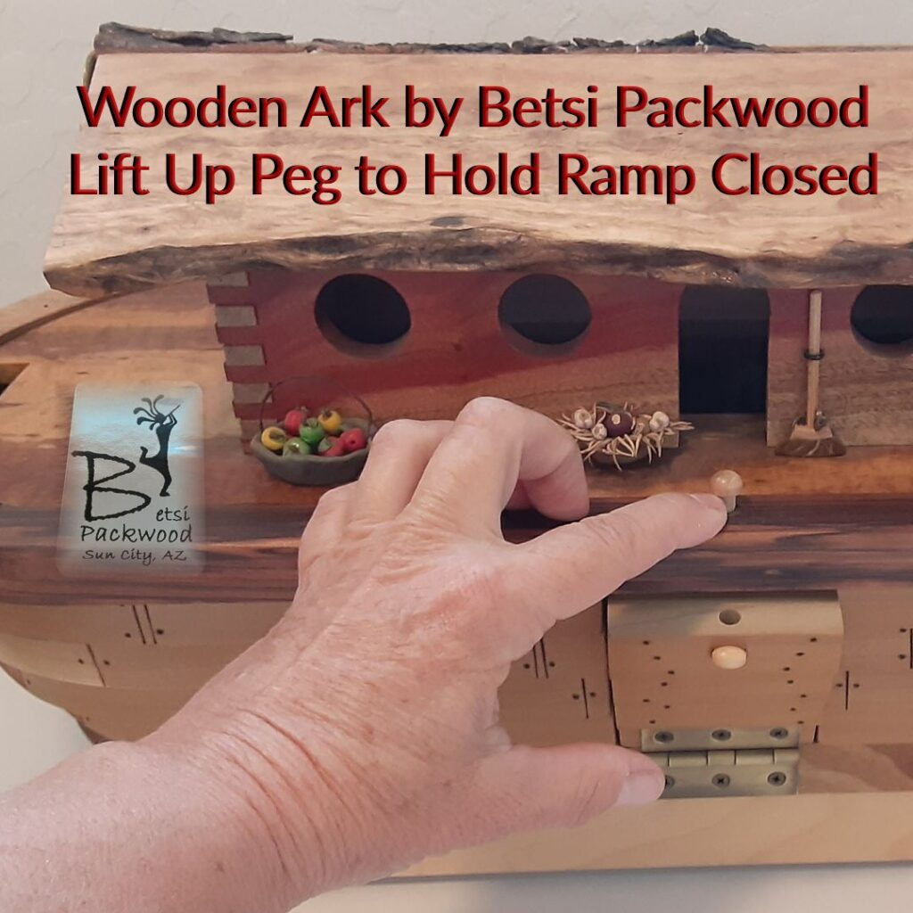 Wooden Ark by Betsi Packwood has a wooden peg for lifting up and then closing down to hole the animal walk up and down ramp in place when closed.